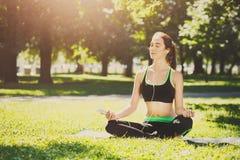 A jovem mulher fora, relaxa a pose da meditação fotografia de stock
