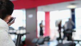 Jovem mulher furada com o boxe de treino de observação do pugilista do smartphone com o saco de perfurador no gym filme