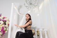 Jovem mulher glamoroso que joga a harpa Imagens de Stock