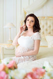 A jovem mulher grávida da morena senta-se em um interior bonito com rosas Fotografia de Stock