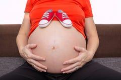 A jovem mulher grávida guarda sapatas para recém-nascido imagens de stock royalty free