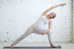 Jovem mulher grávida que faz a ioga pré-natal Parsvakonasana de Utthita imagem de stock royalty free