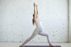 Jovem mulher grávida que faz a ioga pré-natal Pose do guerreiro um imagem de stock royalty free