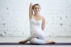 Jovem mulher grávida que faz a pose pré-natal de Gomukhasana da ioga foto de stock royalty free