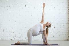 Jovem mulher grávida que faz a posição prolongada pré-natal da ioga do ângulo lateral imagens de stock royalty free