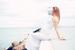 Jovem mulher grávida que relaxa no beira-mar fotografia de stock royalty free