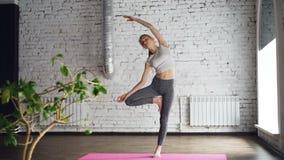 A jovem mulher gracioso está fazendo a pose praticando Vriksasana da árvore da ioga durante a classe individual no centro do bem- vídeos de arquivo