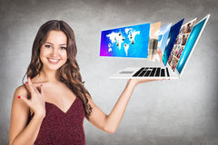A jovem mulher guarda o portátil Foto de Stock Royalty Free