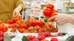 A jovem mulher guarda o saco de plástico branco e escolhe tomates video estoque
