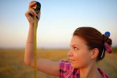 A jovem mulher guarda a roleta do tapeline no as mãos no campo Imagens de Stock Royalty Free