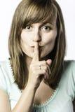 A jovem mulher guarda um dedo a sua boca Imagem de Stock Royalty Free