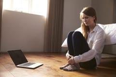 Jovem mulher infeliz que está sendo tiranizada em linha com portátil Fotos de Stock Royalty Free