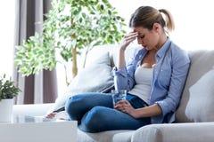 Jovem mulher insalubre com a dor de cabeça que guarda o vidro da água ao sentar-se no sofá em casa imagem de stock
