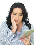 Jovem mulher interessada chocada amedrontada que guarda uma tabuleta sem fio Fotografia de Stock Royalty Free