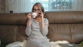 A jovem mulher interessada tem uma conversa telefônica e um chá bebendo filme