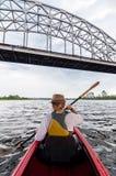 Jovem mulher irreconhecível que kayaking em um rio Menina feliz que canoeing sob a ponte do metal em um dia de verão imagens de stock royalty free