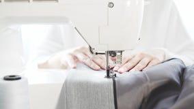 A jovem mulher irreconhecível s entrega costurar um revestimento em uma máquina de costura, negócio video estoque