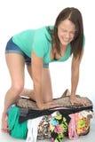 Jovem mulher irritada forçada frustrante que tenta fechar uma mala de viagem de transbordamento Imagem de Stock
