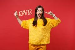 A jovem mulher irritada na camiseta amarela da pele que guarda letras de madeira da palavra ama apontar o indicador na cabeça, ju fotos de stock
