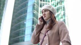 Jovem mulher irritada que fala no telefone entre construções altas Fotos de Stock