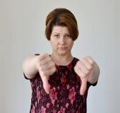 Jovem mulher irritada que mostra o polegar para baixo Fotografia de Stock Royalty Free