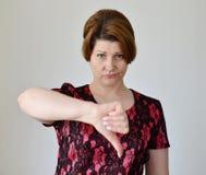 Jovem mulher irritada que mostra o polegar para baixo Fotografia de Stock