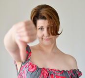 Jovem mulher irritada que mostra o polegar para baixo Imagem de Stock Royalty Free