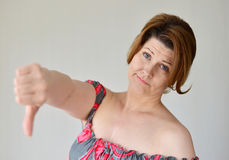 Jovem mulher irritada que mostra o polegar para baixo Imagem de Stock