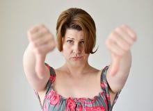 Jovem mulher irritada que mostra o polegar para baixo Imagens de Stock Royalty Free