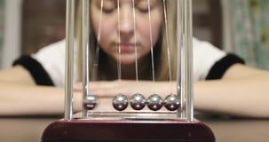 A jovem mulher joga com um berço do ` s de Newton video estoque