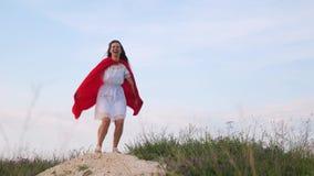 A jovem mulher joga em um casaco vermelho com express?o dos sonhos sonhos da menina de transformar-se um super-her?i super-her?i  vídeos de arquivo