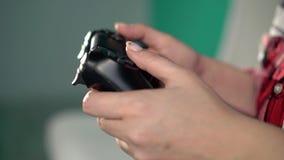 A jovem mulher joga o jogo de vídeo usando um gamepad closeup filme