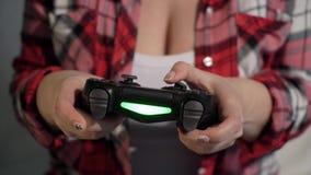 A jovem mulher joga o jogo de vídeo usando um gamepad closeup video estoque