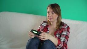 A jovem mulher joga o jogo de vídeo usando um gamepad closeup vídeos de arquivo