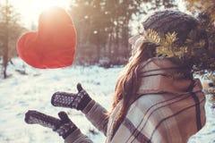 A jovem mulher joga um coração vermelho do descanso na floresta do inverno imagem de stock royalty free