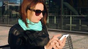 A jovem mulher lê mensagens no telefone filme
