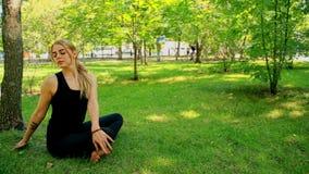 Jovem mulher larga do tiro que faz a ioga no parque vídeos de arquivo