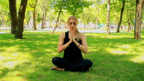 Jovem mulher larga do tiro que faz a ioga no parque video estoque