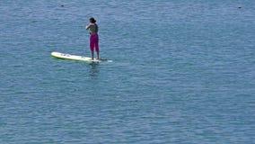 A jovem mulher levanta-se o embarque da pá no lago azul video estoque