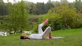 A jovem mulher levanta seu pé ao encontrar-se em uma esteira da ioga em um banco de rio vídeos de arquivo