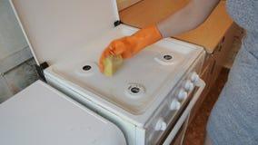 A jovem mulher limpa o fogão vídeos de arquivo