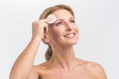 A jovem mulher limpa a pele da cara Fotografia de Stock Royalty Free