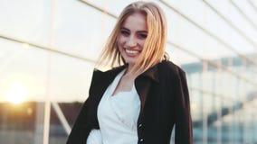 A jovem mulher lindo anda em uma luz do sol brilhante, gerencie para a câmera e sorri felizmente Humor alegre, estando feliz vídeos de arquivo