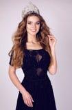 Jovem mulher lindo com cabelo escuro no vestido luxuoso com coroa preciosa foto de stock
