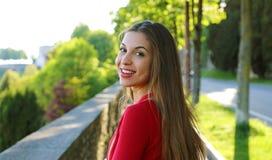 A jovem mulher lindo com cabelo longo gerencie a cabe?a e a vista da c?mera ao andar na rua foto de stock royalty free