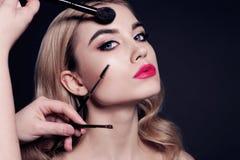 A jovem mulher lindo com o cabelo louro, fazendo compõe foto de stock