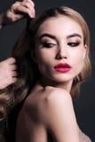 A jovem mulher lindo com o cabelo louro, fazendo compõe foto de stock royalty free