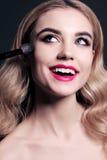 A jovem mulher lindo com o cabelo louro, fazendo compõe imagens de stock royalty free
