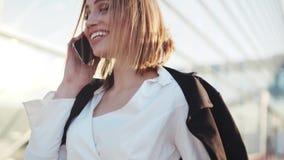 A jovem mulher lindo em uma blusa branca à moda que fala felizmente em seu telefone, dá um sorriso bonito, ri Negócios filme