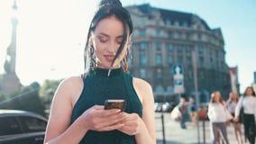 A jovem mulher lindo em uma luz solar brilhante usa seu telefone quando estar no centro da cidade, texts contentemente para trás, filme